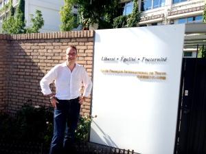 Matthieu Séguéla, ancien conseiller consulaire, devant la devise républicaine inscrite à l'entrée du Lycée français de Tokyo